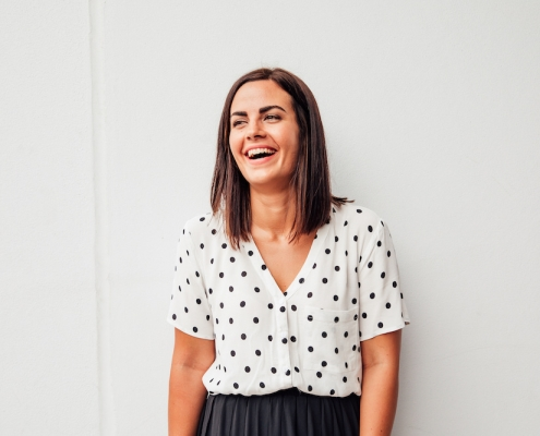 Leanne Webber Smiling in front of white wall