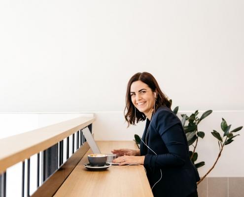 Leanne Webber sitting at light wooden desk with laptop
