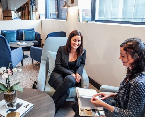 Two women laughing and sitting at a coffee table