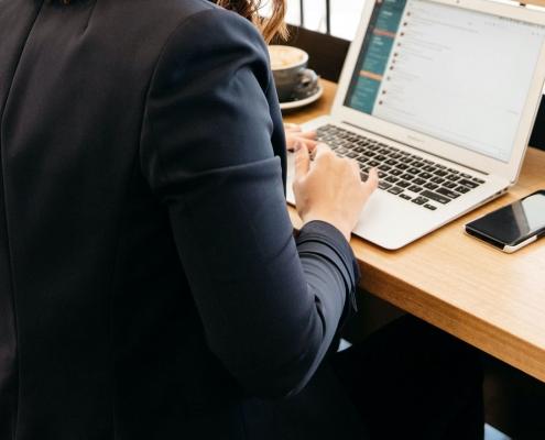 Leanne Webber wearing black blazer while working on laptop