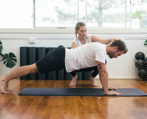 Man doing pilates on wooden floor with instructor