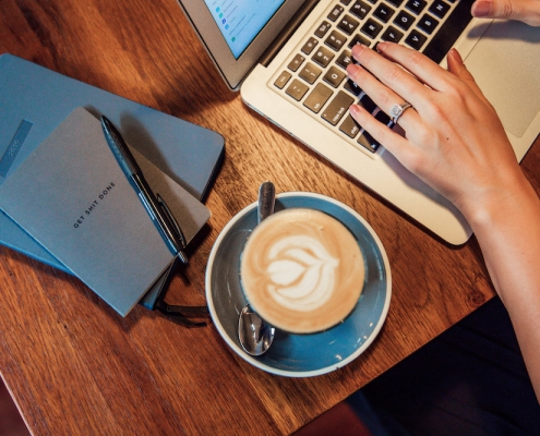 Blue notebooks, cup of coffee and hands working on a laptop