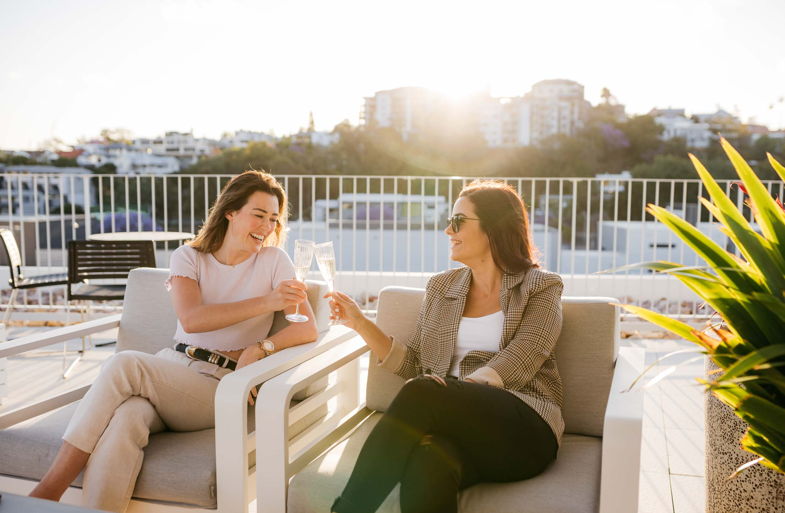 Confident business owners Leanne and Steph clinking wine glasses