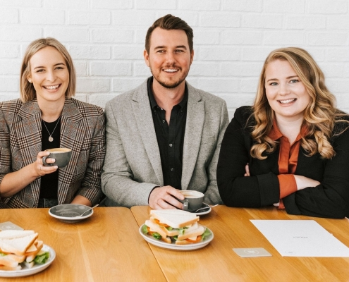 The team at Club Sandwich HR smiling with sandwiches at a cafe